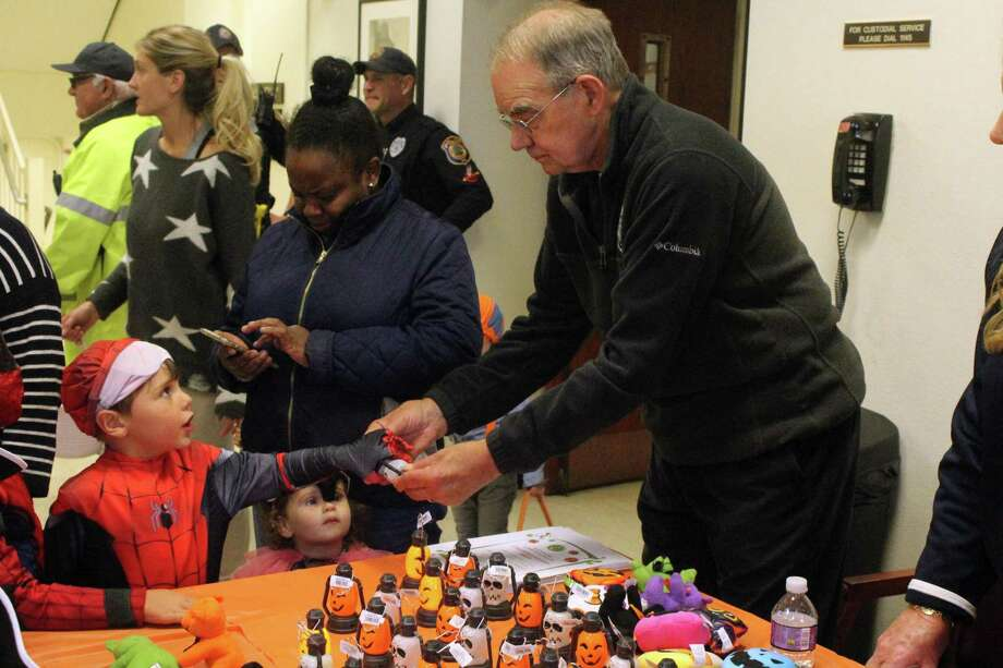Joe Nixon, of Westport PAL, shows young trick-or-treaters some of the goodies offered at a table in town hall for the annual Halloween parade. Taken Oct. 29, 2019 in Westport, Conn. Photo: DJ Simmons/Hearst Connecticut Media