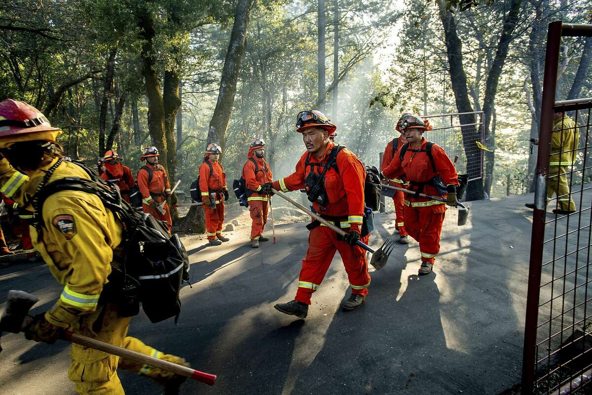 Inmate firefighters battle the Kincade Fire near Healdsburg, Calif., on Tuesday, Oct. 29, 2019. Millions of people have been without power for days as fire crews race to contain two major wind-whipped blazes that have destroyed dozens of homes at both ends of the state: in Sonoma County wine country and in the hills of Los Angeles. (AP Photo/Noah Berger)