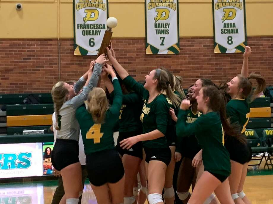 Dow High's volleyball team celebrates its overall Saginaw Valley League title after edging Grand Blanc in a thrilling five-set showdown Tuesday at the Chargers' gym. Photo: Fred Kelly/fred.kelly@mdn.net