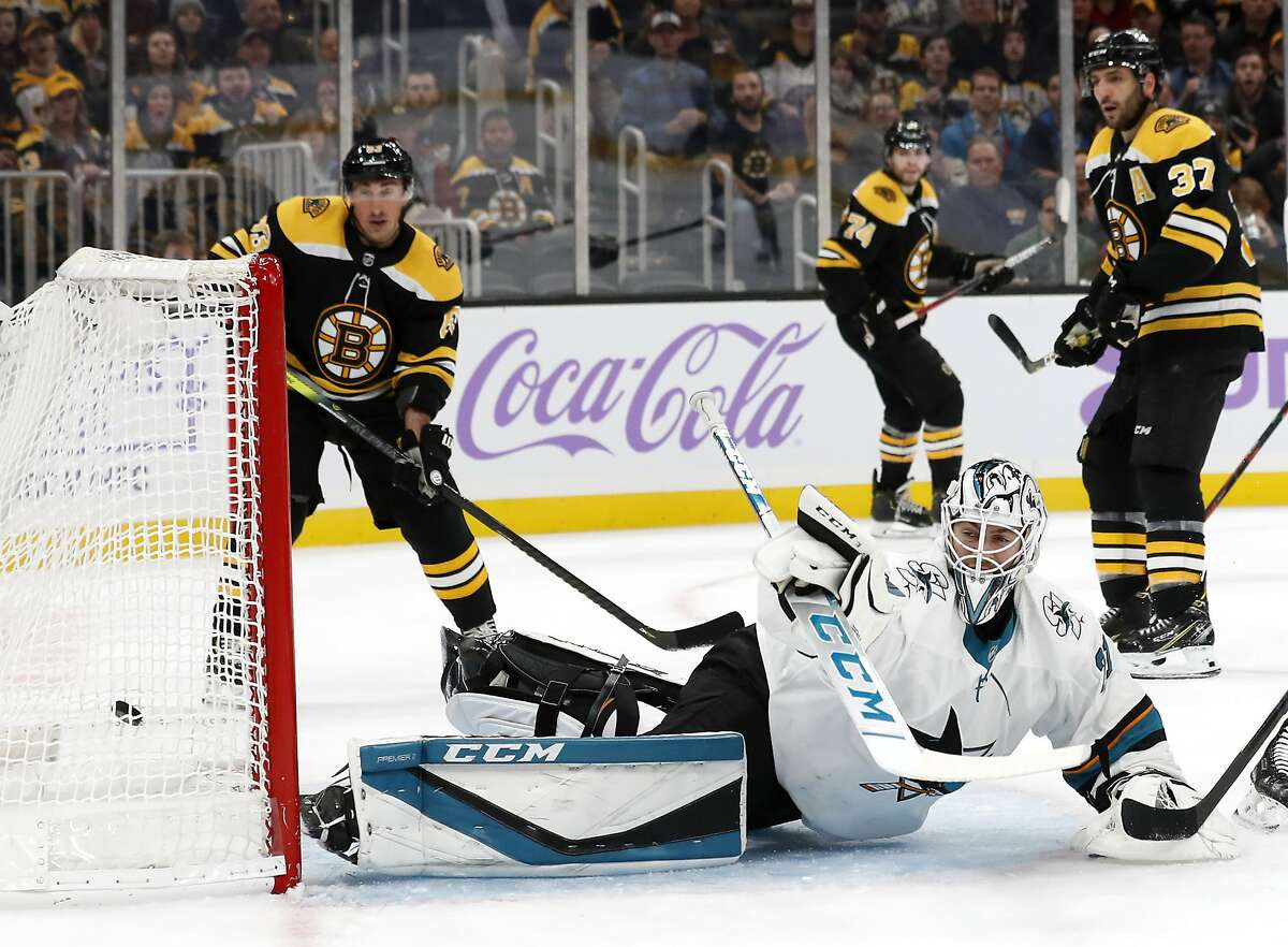 As Boston Bruins' Patrice Bergeron (37) and Brad Marchand look on, San Jose Sharks goaltender Martin Jones can't stop a goal by Boston Bruins' David Pastrnak during the first period of an NHL hockey game, Tuesday, Oct. 29, 2019, in Boston. (AP Photo/Winslow Townson)
