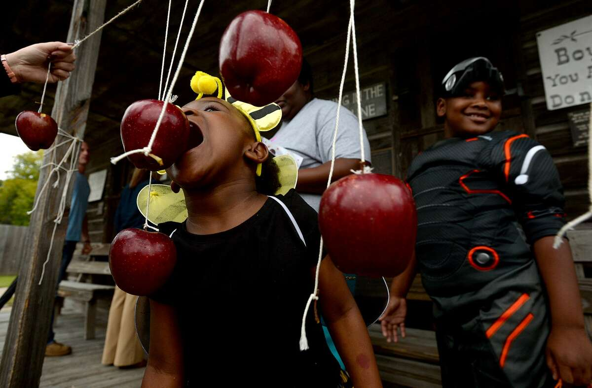Jakirah Davis tries to snag an apple as her brother Jeffery Davis awaits his turn at the game while taking in the activities at the annual Spindletop - Gladys City Boomtown Museum's Spindletop Spookfest Tuesday. Photo taken Tuesday, October 29, 2019 Kim Brent/The Enterprise