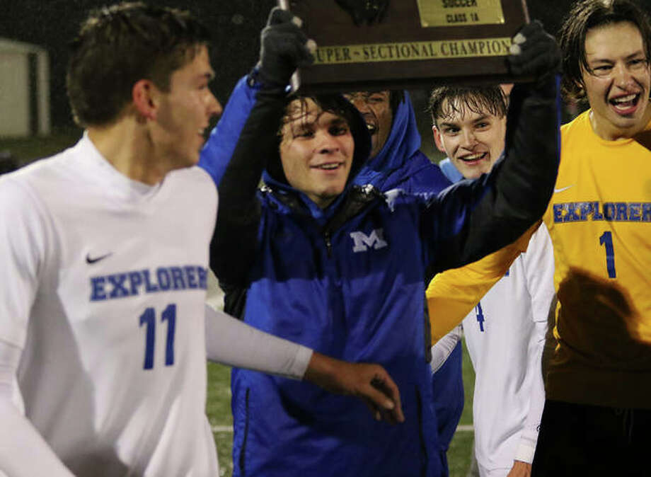 Injured Explorer Aaron Boulch takes the super-sectional plaque back to teammates with goalie Joe Guehlstorf (1) and Nick LaFata (11) on Tuesday night after beating Columbia 2-1 in the Breese Mater Dei Class 1A Super-Sectional. Photo: Greg Shashack | The Telegraph