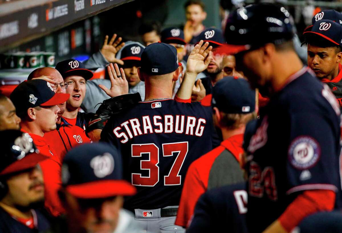 Nationals teammates greet starting pitcher Stephen Strasburg during the sixth inning Tuesday. Strasburg went 5-0 in the postseason and recorded 35 strikeouts.