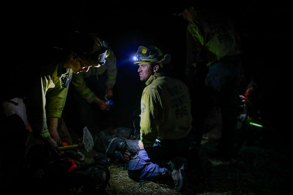Firefighters eat dinner as they monitor the Kincade fire in Windsor, California, on Tuesday, Oct. 29, 2019.