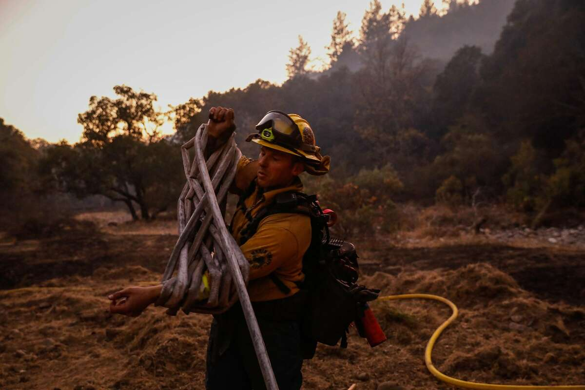 Firefighters Craig Fowler rolls hose off of Leslie Road while monitoring the Kincade fire in Windsor, California, on Tuesday, Oct. 29, 2019.