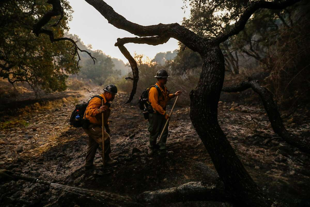 Firefighters mop up off of Leslie Road during the Kincade fire in Windsor, California, on Tuesday, Oct. 29, 2019.