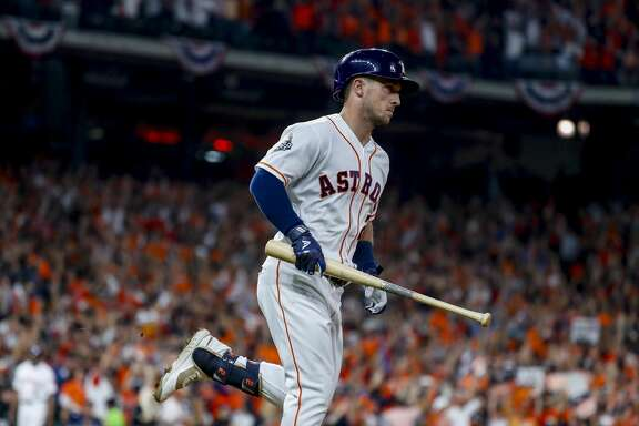 Houston Astros third baseman Alex Bregman (2) holds onto his bat as he runs to first after hitting a solo home run to give the Astros a 2-1 lead during the first inning of Game 6 of the World Series at Minute Maid Park on Tuesday, Oct. 29, 2019, in Houston.