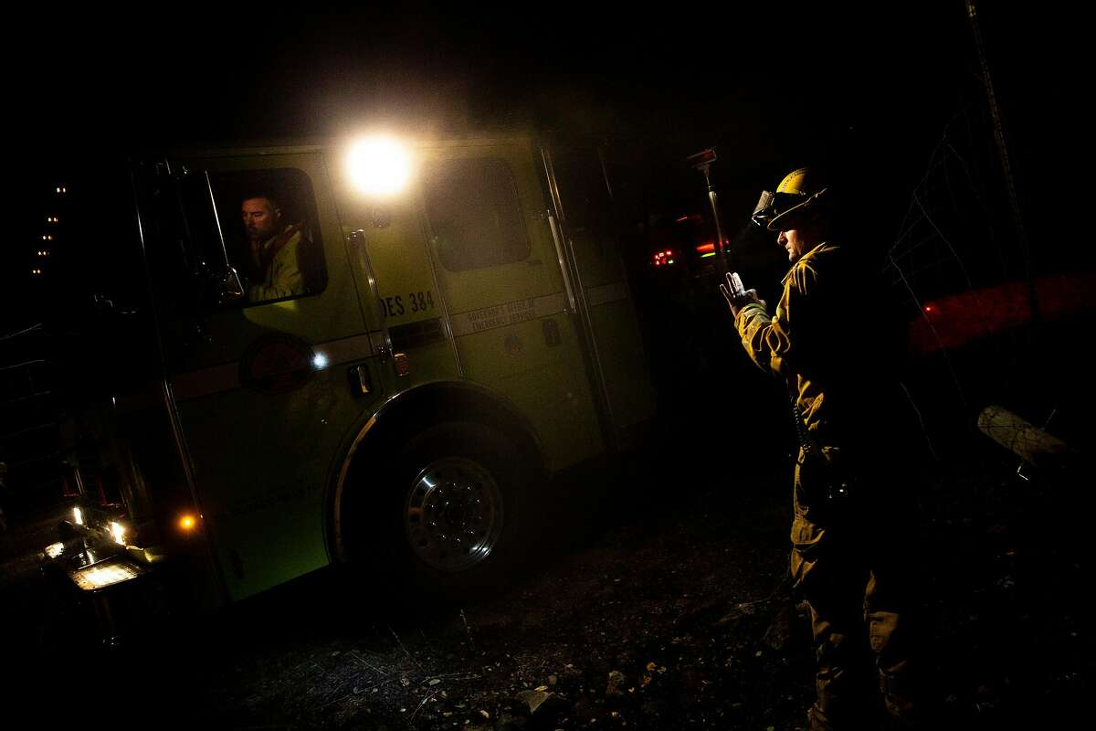 John Van Dalen of the El Dorado Hills Fire Department helps the truck back up and out to Chalk Hill Road as they monitor for hot spots in the area during the Kincade Fire on Tuesday, Oct. 29, 2019, in Windsor, Calif.