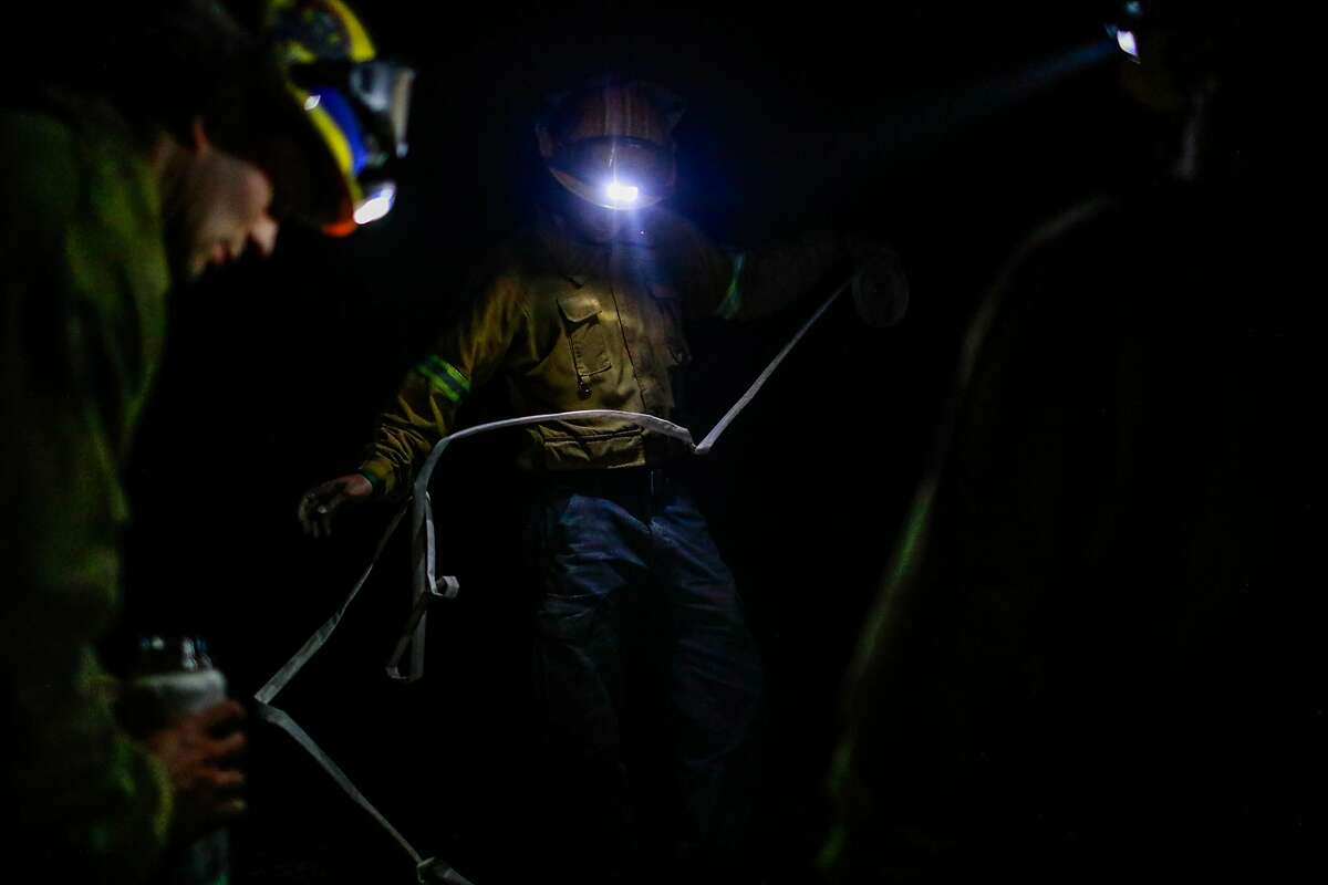 Firefighters wrap up their hose at night during the Kincade fire in Windsor, California, on Tuesday, Oct. 29, 2019.
