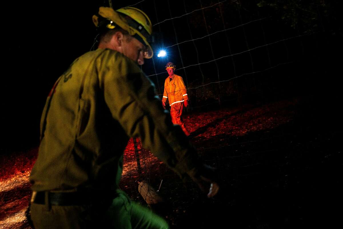El Dorado Hills firefighters monitor the area for spot fires along Chalk Hill Road during the Kincade Fire on Tuesday, Oct. 29, 2019, in Windsor, Calif.