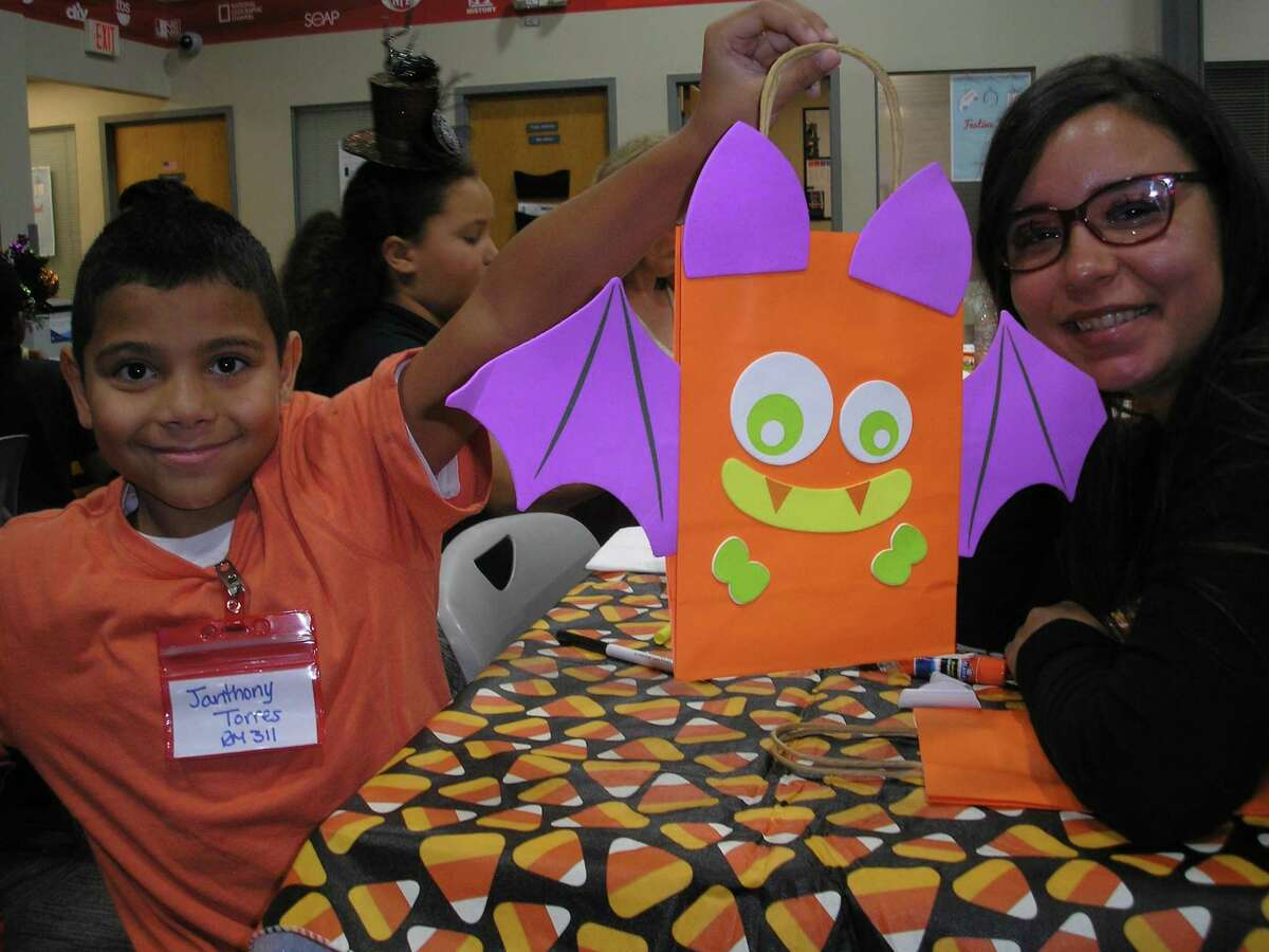"""Shelton resident Denisse Ramos, right, is a mentor in the """"Beyond School Walls"""" mentoring program at her company, Comcast in Berlin. The 11-year-old program is sponsored by Comcast and managed by Nutmeg Big Brothers Big Sisters. At a recent mentoring session, Ramos and her mentee, Janthony, celebrated Halloween with holiday-related snacks, games and trick or treating at Comcast's Berlin headquarters. Janthony and 24 other students from New Britain's Lincoln Elementary School are mentees in """"Beyond School Walls."""""""