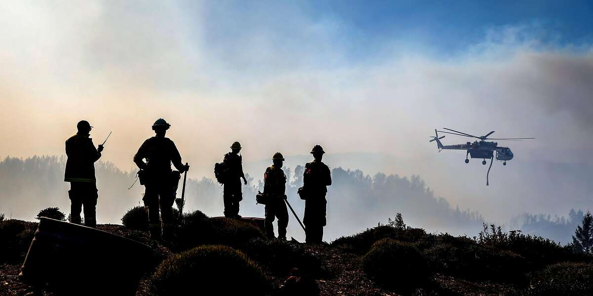 Firefighters watch as a helicopter drops water over the Kincade Fire near Ida Clayton Road in Calistoga, California, on Tuesday, Oct. 29, 2019.