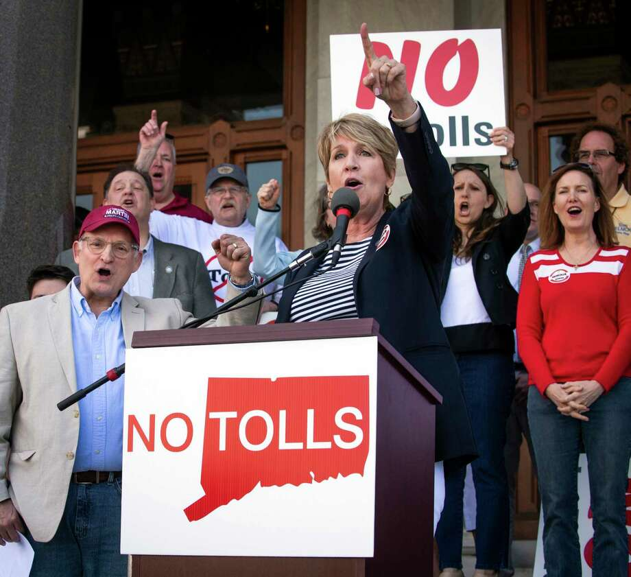 """State Rep. Laura Devlin addresses the crowd of anti-toll protesters in front of the Capitol Building, May 18 in Hartford. Protesters have gathered outside the state Capitol to rally against a proposal to put electronic tolls on the state's highways. Demonstrators on Saturday called the plan another tax increase state residents can't afford. They held """"no tolls"""" signs and wore """"no tolls"""" shirts as they criticized Democratic Gov. Ned Lamont's plan to raise money for highway improvements. Photo: Melanie Stengel / Associated Press / HOT ROD 50"""