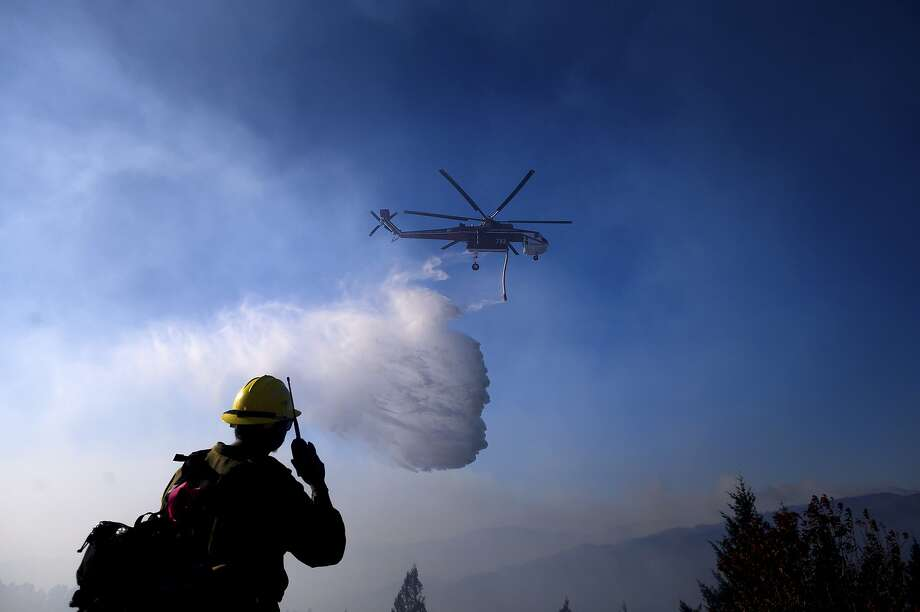 A helicopter drops water while battling the Kincade Fire near Healdsburg, Calif., on Tuesday, Oct. 29, 2019. Millions of people have been without power for days as fire crews race to contain two major wind-whipped blazes that have destroyed dozens of homes at both ends of the state: in Sonoma County wine country and in the hills of Los Angeles. (AP Photo/Noah Berger) Photo: Noah Berger / Associated Press