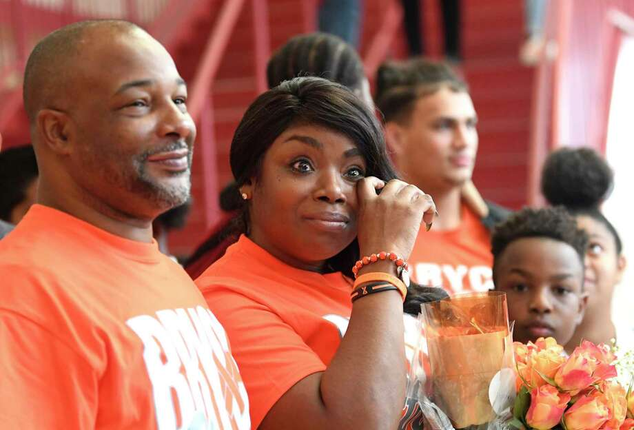 Diana Wisdom wipes a tear as she stands by her husband, Rich Wisdom, during a gathering at Judson High School for their son, Bryce. / San Antonio Express-News