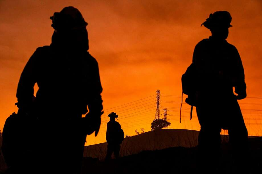 CORRECTION - Members of an inmate firefighting crew are silhouetted against a hillside with a track of PG&E lines during firefighting operations to battle the Kincade Fire in Healdsburg, California on October 26, 2019. - US officials on October 26 ordered about 50,000 people to evacuate parts of the San Francisco Bay area in California as hot dry winds are forecast to fan raging wildfires. (Photo by Philip Pacheco / AFP) / The erroneous source appearing in the metadata of this photo by Philip Pacheco has been modified in AFP systems in the following manner: [AFP] instead of [www.philippachecophoto.com]. Please immediately remove the erroneous mention from all your online services and delete it from your servers. If you have been authorized by AFP to distribute it to third parties, please ensure that the same actions are carried out by them. Failure to promptly comply with these instructions will entail liability on your part for any continued or post notification usage. Therefore we thank you very much for all your attention and prompt action. We are sorry for the inconvenience this notification may cause and remain at your disposal for any further information you may require. (Photo by PHILIP PACHECO/AFP via Getty Images) Photo: Philip Pacheco, AFP Via Getty Images