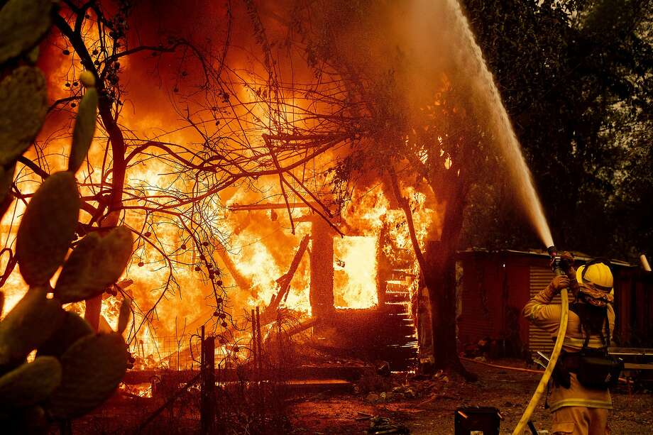 A firefighter sprays water on a burning home as the Kincade Fire burns through the Jimtown community of unincorporated Sonoma County, Calif., on Thursday, Oct. 24, 2019. (AP Photo/Noah Berger) Photo: Noah Berger, Associated Press