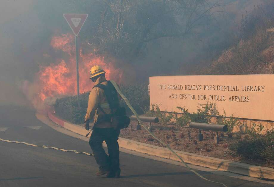 Firefighters battle wildfires near the Reagan Library in Simi Valley. The flames came within 30 yards of the property, which was protected by aircraft dropping water and by a buffer zone chewed by goats. Photo: Mark Ralston / AFP Via Getty Images