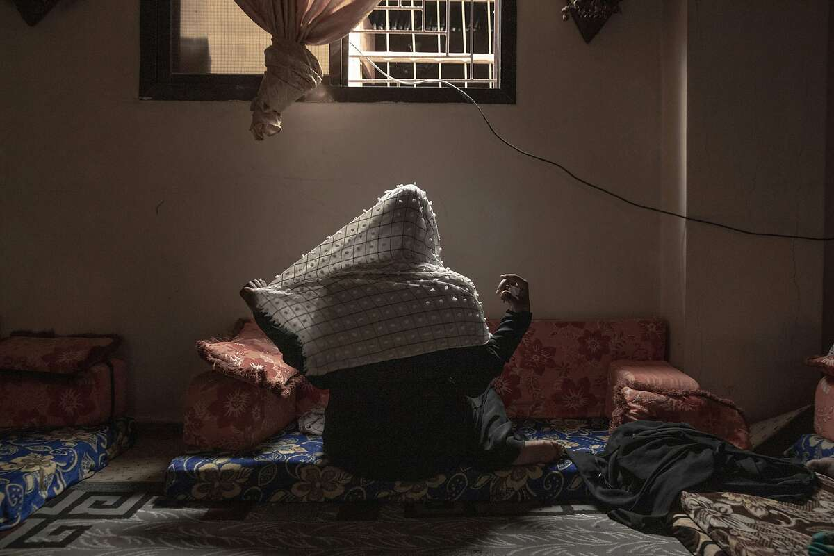 In this July 20, 2019 photo, 20-year-old Ethiopian migrant Zahra, a rape victim, adjusts her veil for a photograph, in Basateen, a district of Aden, Yemen. She was imprisoned for a month in a tin-roofed hut, broiling and hungry, ordered to call home each day to beseech her family to wire $2,000. She said she did not have family to ask for money and pleaded for her freedom. Instead, her captors raped her. (AP Photo/Nariman El-Mofty)