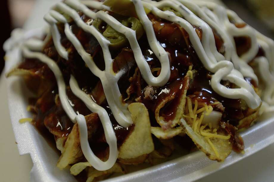 The Redneck nachos, a popular menu item at Chuck's BBQ & Burgers in Evadale, is hearty helping of homemade potato chips topped with chopped beef, cheese, onions, jalapeños, homemade bbq sauce and sour cream. Photo taken Wednesday, March 4, 2015 Kim Brent/The Enterprise Photo: Kim Brent / Kim Brent/The Enterprise / Beaumont Enterprise
