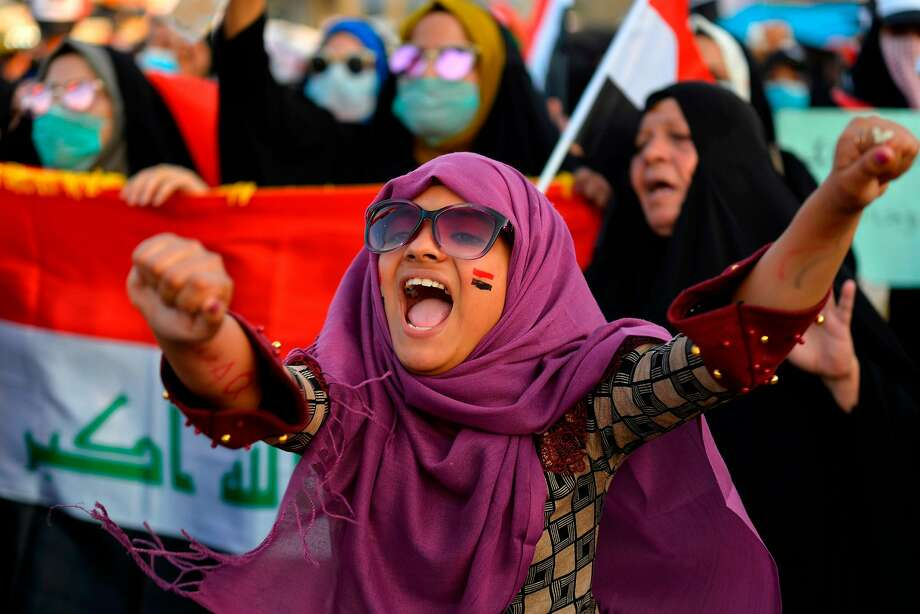 Iraqi women wave their national flag during during anti-government protests in the city of Najaf. Photo: AFP Via Getty Images