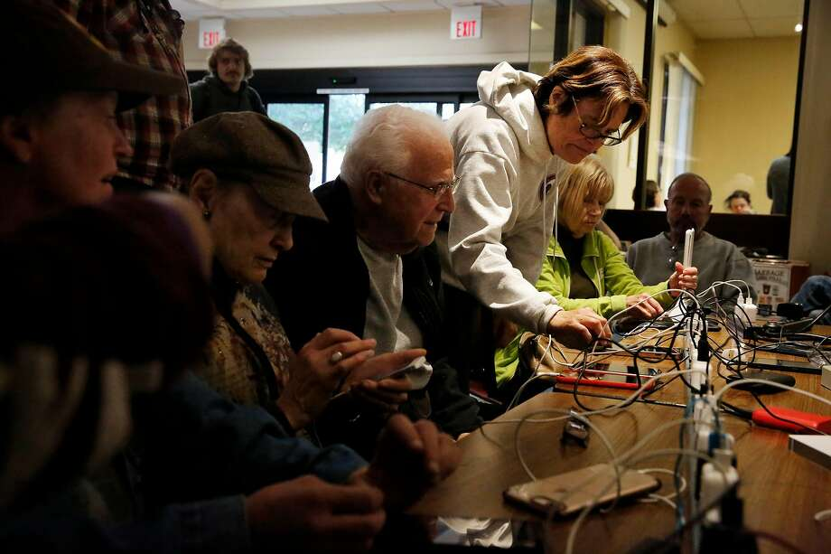 Heather Eben (standing) of San Rafael charges her cell phone along with other people charging devices on a power strip at the Community Center on Tuesday, October 29, 2019 in San Rafael, Calif. During the mass outages, many people lost cell phone service as well as power. Photo: Lea Suzuki / The Chronicle