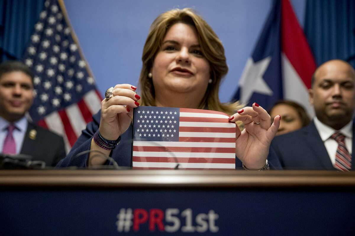 Resident Commissioner Jenniffer Gonzalez-Colon, who represents Puerto Rico as a nonvoting member of Congress, holds up an American flag with 51 stars, speaks about Puerto Rico statehood during a news conference on Capitol Hill in Washington, Tuesday, Oct. 29, 2019. (AP Photo/Andrew Harnik)