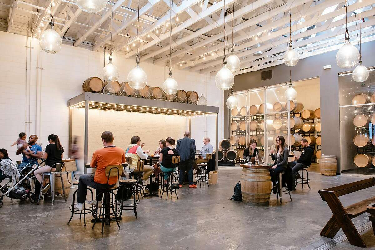Guests drink wine on the main wine production floor that doubles as a tasting area when wine making has finished, at Bluxome Winery in San Francisco, California, on Friday, Oct. 25, 2019.