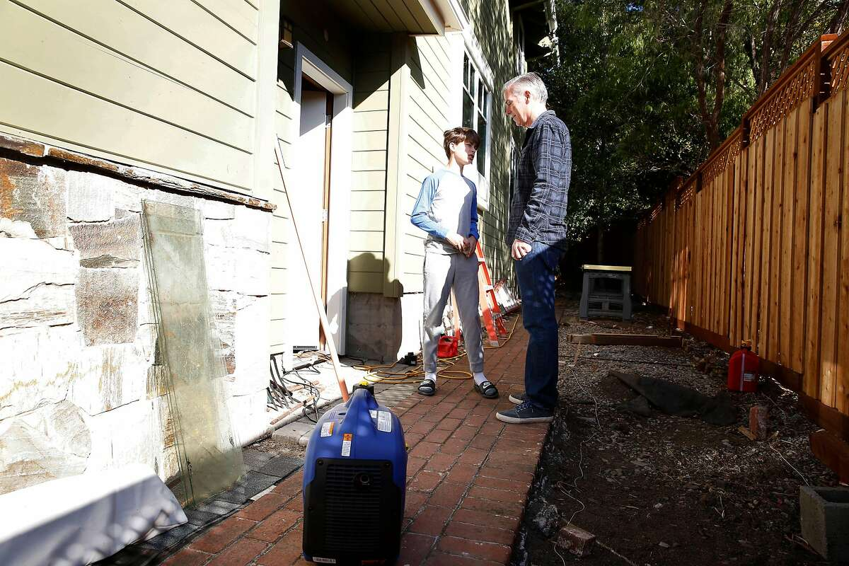 Dan Schalit (right) talks with his son Lucca Hurst-Schalit (left) as they walk past a generator that has been helping provide a little power to their home on Wednesday, October 30, 2019 in Mill Valley, Calif. Dan Schalit was able to borrow a generator from a friend while they had no electricity.