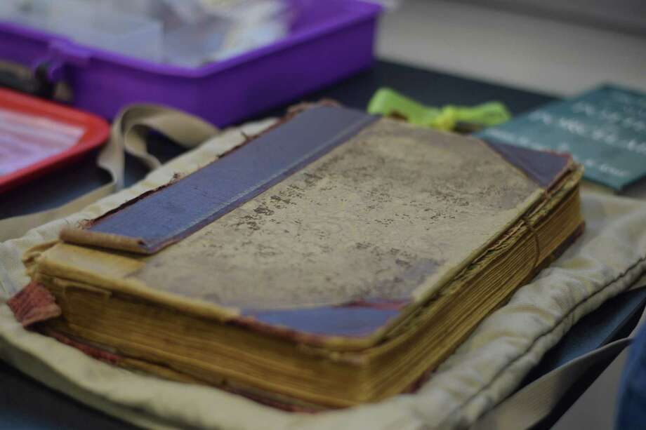 The Red Ledger is an original ledger for the Olivewood Cemetery, where many black residents are buried. David Bruner's team of Lone Star College-CyFair students and researchers have been scanning the document carefully and making it into a PDF document. Photo: Chevall Pryce