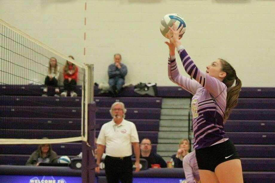 Middle blocker Emily Loney sets the ball over the net during a loss to Leland on Oct. 22. (File photo)