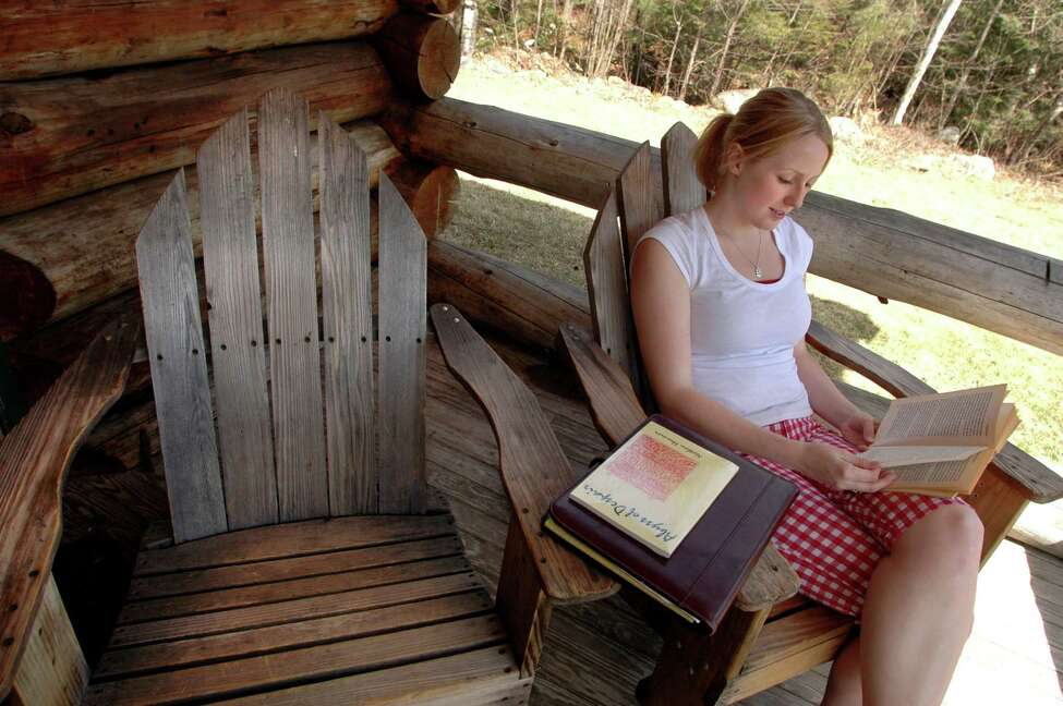 Times Union staff photo by Cindy Schultz Kristin Thorpe, 21, of Crown Point, reads by an Adirondack cabin Saturday, April 16, 2005, at Dippikill in Warren County, N.Y.