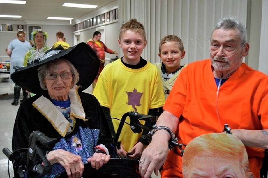 Helen Crawford, left, her son Dennis Crawford, right, and her two great great grandsons, pose for a photo last weekend at her 100th birthday party in Gladwin. (Ashley Schafer/Ashley.Schafer@hearstnp.com)