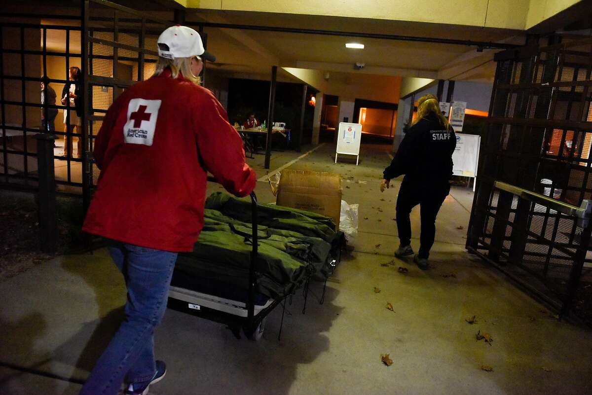 Red Cross shelter manager Michelle Romero and Community Services Department employee, Anna Grant, bring supplies and cots into the Healdsburg Community Center shelter which opened as an evacuation center due to the Kincade Fire in Sonoma County on October 24, 2019 in Healdsburg, Calif.