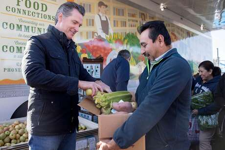 California Governor Gavin Newsom hands out apples to evacuees in line at the Redwood Empire Mobile Food Bank parked at the Kaiser Permanente parking lot in Santa Rosa, Calif. Wednesday, Oct. 30, 2019.