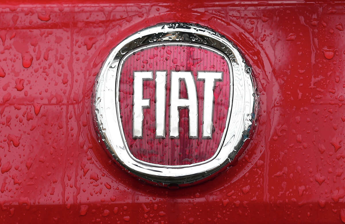 FILE - In this Jan. 2, 2014 file photo, a Fiat logo pictured on a car in Milan, Italy. Italian-American carmaker Fiat Chrysler Automobiles on Wednesday, Oct. 30, 2019 confirmed that it is in talks with French rival PSA Peugeot, its second bid this year to reshape the global auto industry facing huge challenges with the transition to electric and autonomous vehicles. (AP Photo/Antonio Calanni, File)