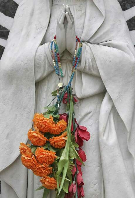 Flowers hang from a Virgin de Guadalupe statue in on All Souls Day.