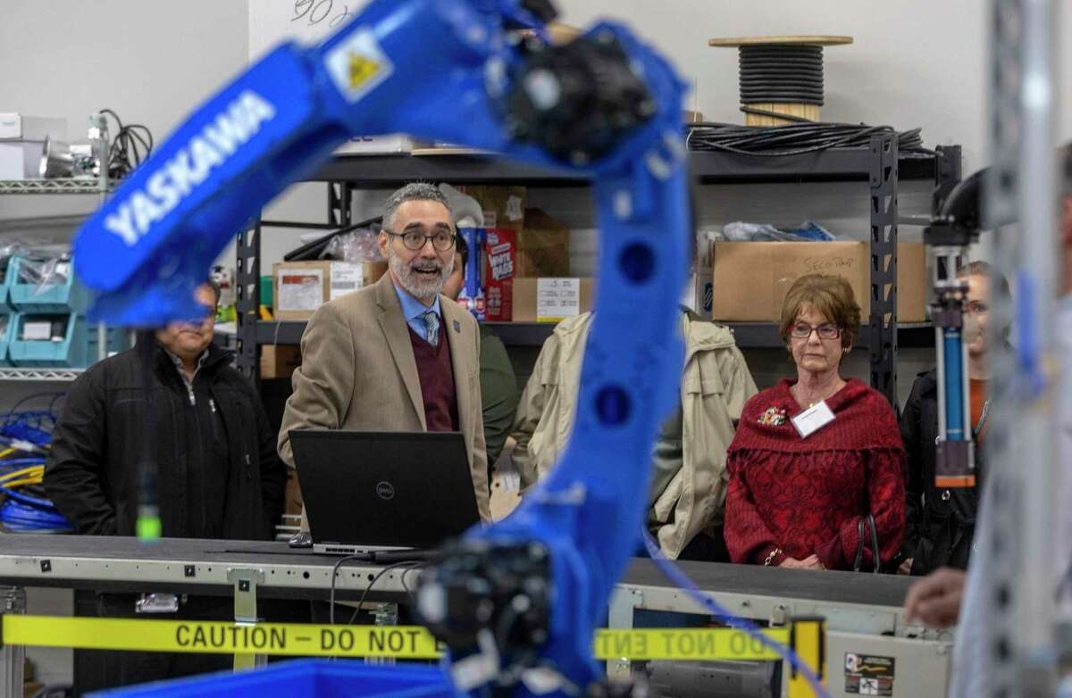 Erik Nieves, Plus One Robotics CEO and co-founder, framed by robot arm, talks Wednesday, Oct. 30, 2019 after the ribbon cutting of the company's new 11,000 square foot facility at Port San Antonio about the company's products.