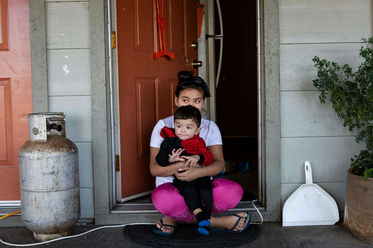 Angellee Ribas, 10, holds her baby brother, Fernando, 1, outside their apartment complex during the power outage in Ukiah, Calif. on Wednesday, October 30, 2019.