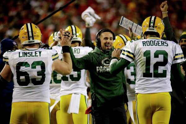 Green Bay Packers head coach Matt LaFleur greets quarterback Aaron Rodgers (12) and center Corey Linsley (63) after a touchdown against the Kansas City Chiefs during the first half of an NFL football game in Kansas City, Mo., Sunday, Oct. 27, 2019. (AP Photo/Charlie Riedel)