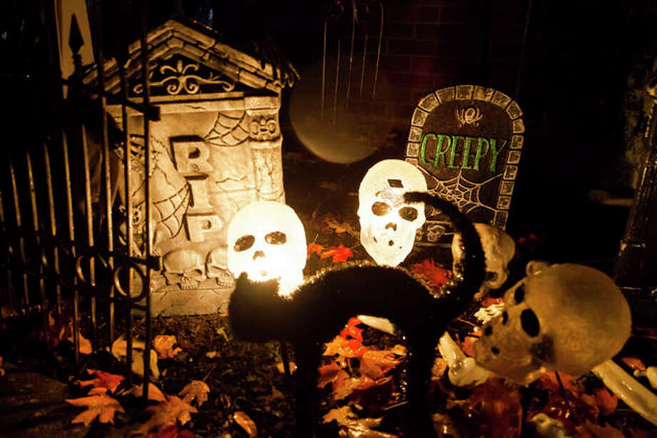 A black cat and graveyard are among the many Halloween decorations in front of Terry Bagley's house on Grandview Avenue in Alton, where many adults bring their kids because they used to trick-or-treat at the same area as kids. Photo: By Jeanie Stephens|The Telegraph