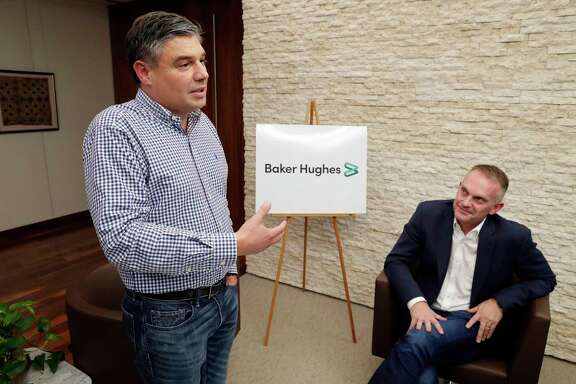 Baker Hughes CEO Lorenzo Simonnelli, left, comments about the new branding logo of Baker Hughes with the downgrading of GE ownership, as Chief Marketing and Technology Officer Derek Mathieson, right, listens during an interview with company officials at their offices Thursday, Oct. 3, 2019 in Houston, TX.