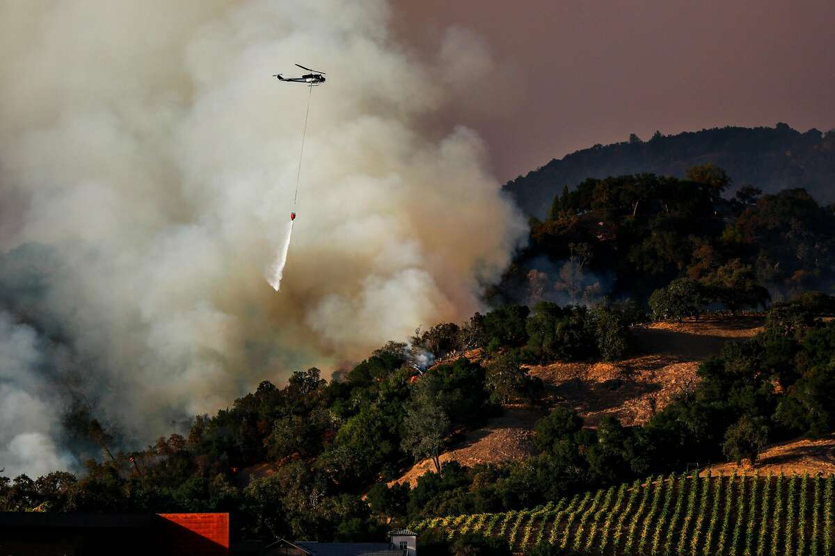 A plane drops water over hill where firefighters worked to contain the Kincade Fire in Geyserville, California, on Thursday, Oct. 24, 2019.