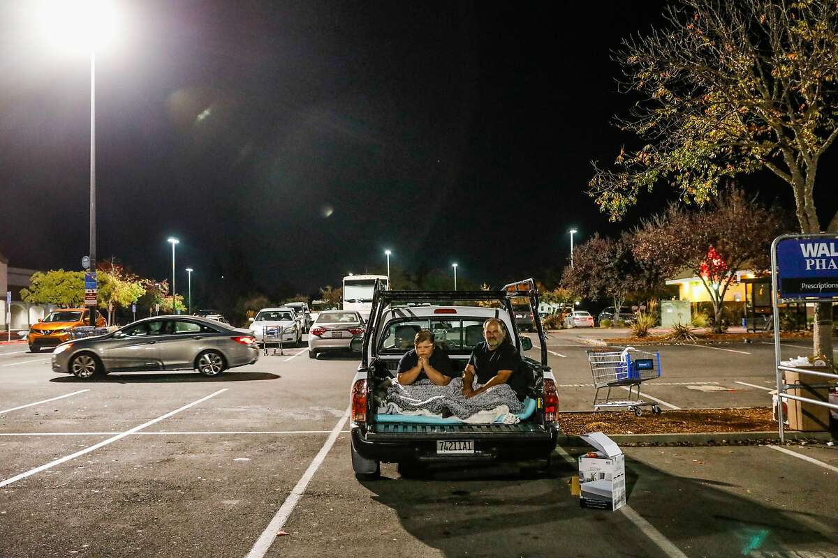 (l-r) Brandon Seeley, 11, and his father Jack Seeley sit for a portrait in the truck of their bed where they will be sleeping after evacuating their home at the Walmart due to the Kincade fire in Rohnert Park, California, on Tuesday, Oct. 29, 2019.