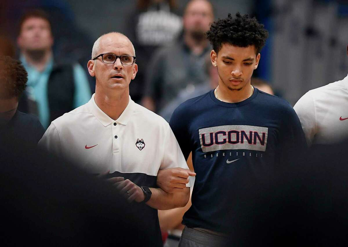 UConn's James Bouknight, right, locks arms with coach Dan Hurley during the national anthem before an October exhibition against Saint Michael'sin Hartford.