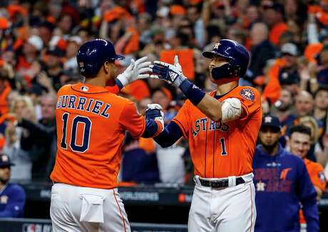 Houston Astros first baseman Yuli Gurriel (10) celebrates his solo home run with Houston Astros shortstop Carlos Correa (1) during the second inning of Game 7 of the World Series at Minute Maid Park on Wednesday, Oct. 30, 2019, in Houston.