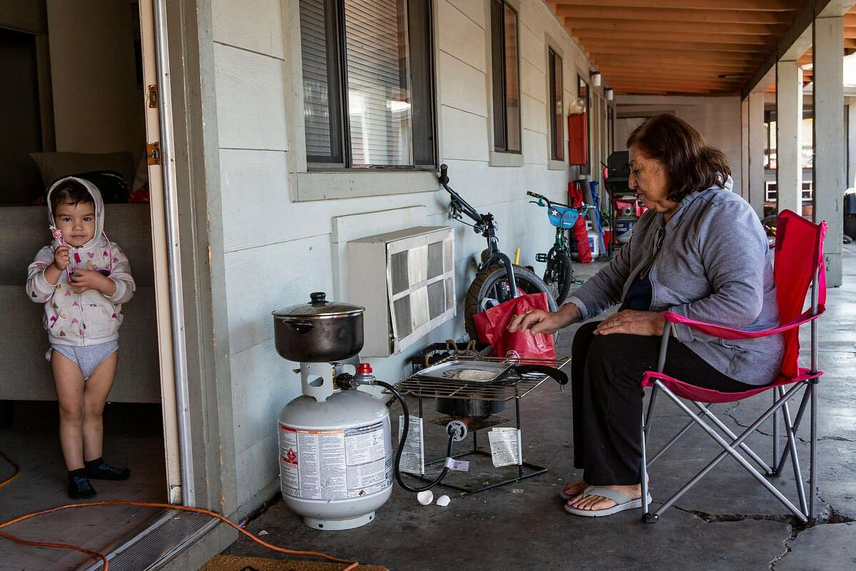 Candela's Aispuro, 72, cooks breakfast while her grandson, Ayleen Zazueta, 2, looks outside their apartment in during the 5 day power outage in Ukiah, Calif. on Wednesday, October 30, 2019.