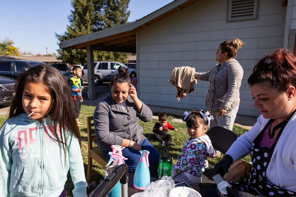 Lisa, a lice technician, helps families get the lice out their kid's hair in the front yard of a Ukiah apartment complex during the 5 day power outage in Ukiah, Calif. on Wednesday, October 30, 2019.