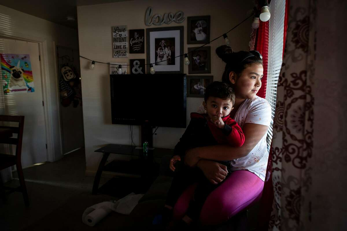 Angellee Ribas, 10, holds her baby brother, Fernando, 1, inside their apartment complex during the power outage in Ukiah, Calif. on Wednesday, October 30, 2019.