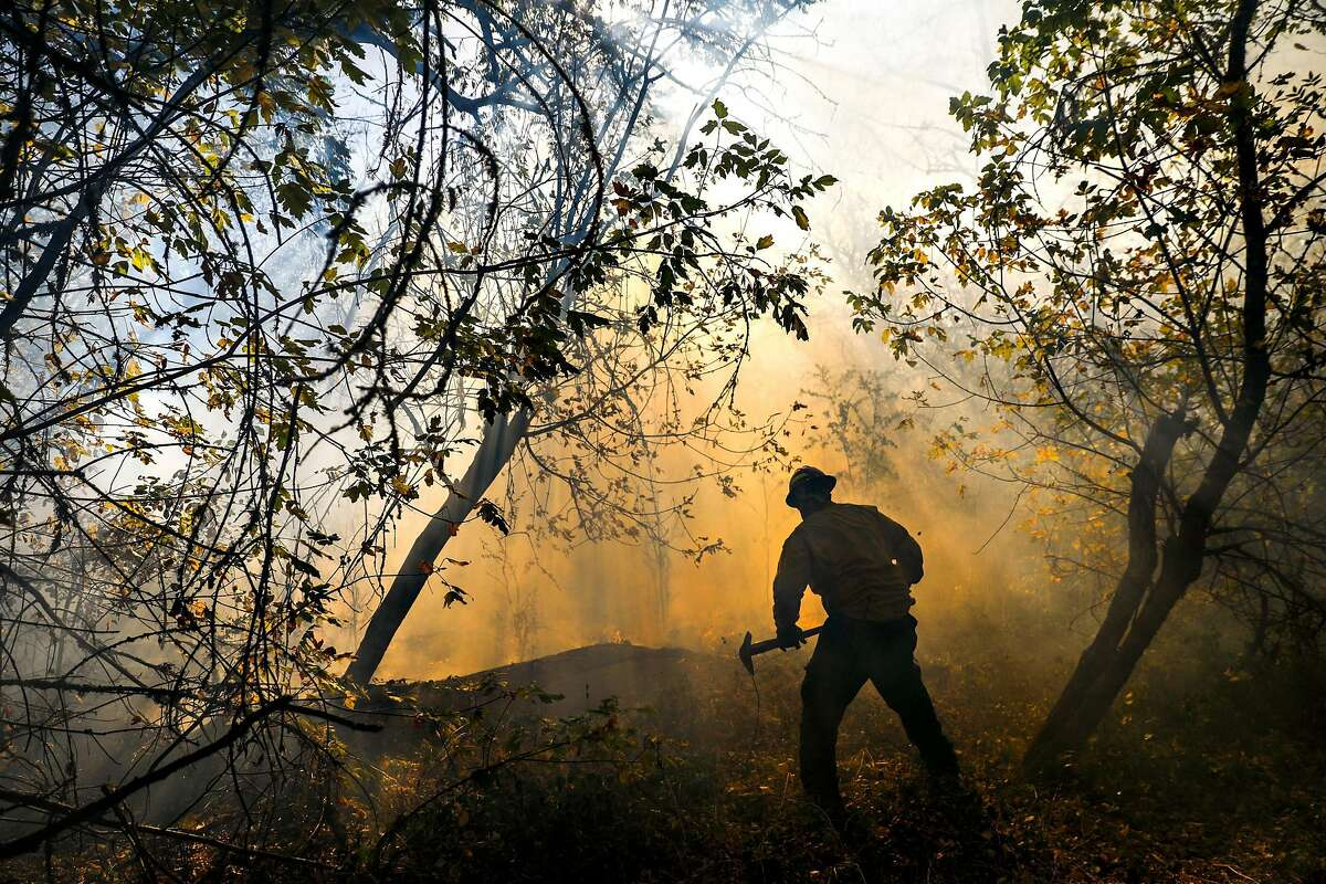 A firefighter works to contain the Kincade fire off of Highway 128 in Healdsburg, California, on Wednesday, Oct. 30, 2019.